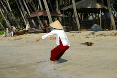 Fisher woman hauling in the fishing net, mui ne, viet nam Stock Photos