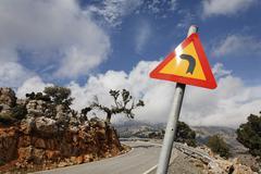 Road sign curves ahead, mountain road, kritsa, crete, greece Stock Photos