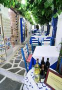 Bottles of wine and blue wooden tables in a tavern, naxos city, cyclades, gre Stock Photos