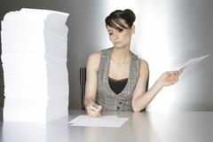 businesswoman, aged 24, taking notes on a silver desktop - stock photo