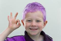 Stock Photo of a four-year-old boy with purple hair wearing a purple sweater