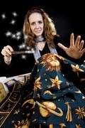Stock Photo of fortune teller holding magic wand and astrology cloth