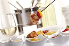 Fondue fork with meat and capsicum in front of a fondue pot Stock Photos