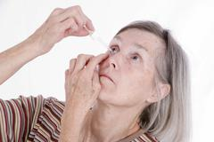 Woman, older than 65 years, using eye drops Stock Photos