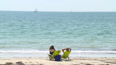 A couple sit on a sunny beach as a schooner passes by in the distance. Stock Footage