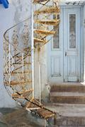 Rusted spiral staircase in front of an old wooden door in naxos, cyclades, gr Stock Photos
