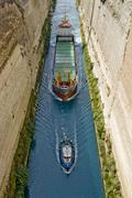 Cargo ship being pulled down a canal, isthmus of corinth, corinth canal, gree Stock Photos