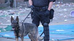 K9 unit with dog during riot with trash and fire in the background Stock Footage