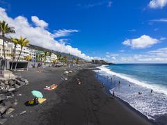 Spain, Balearic Islands, Puerto Naos, Tourists on the black lava beach - stock photo