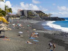 Spain, Canary Islands, La Palma, Puerto Naos, Tourists on the black lava beach - stock photo