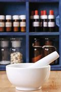 Mortar and pestle in front of an apothecary cabinet full of bottles Stock Photos