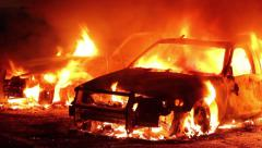 Two police cars fully involved in flames at night in parking lot Stock Footage