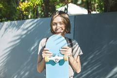 Portrait of smiling young female skate boarder holding her skateboard - stock photo