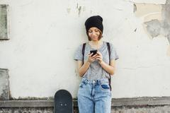 Portrait of smiling young female skate boarder using smartphone - stock photo