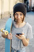 Portrait of smiling young female skate boarder holding smartphone and skateboard - stock photo