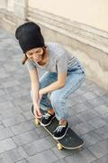Smiling young female skate boarder on her skateboard - stock photo