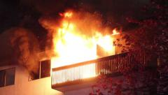 Residential building's balcony fully involved in heavy flames and smoke - stock footage