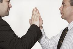 two businessmen doing a high five - stock photo