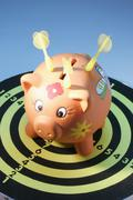 Piggy bank with darts on dart board Stock Photos