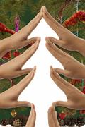 Conceptual christmas tree symbol made from hands with christmas decoration Stock Photos