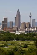 skyline of frankfurt, messeturm tower, horse track and niederrad golf course  - stock photo