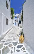 narrow alley with white houses and a yellow clay vase in mykonos, cyclades, g - stock photo
