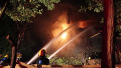 Firemen with hoses putting water on house fire at night - stock footage