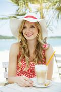 Portrait of smiling young woman with Latte macchiato - stock photo