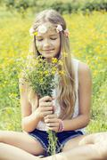 Portrait of a girl sitting on a flower meadow smelling on a bunch of flowers Stock Photos
