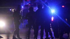 Silhouette of SWAT officers with riffles standing by police truck Stock Footage
