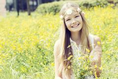 Portrait of a happy girl sitting on a flower meadow wearing flowers Stock Photos