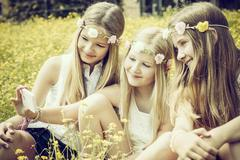 Portrait of three girls wearing floral wreaths taking a selfie on a flower Kuvituskuvat