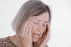 Retired woman, 65 years old, with a headache Stock Photos