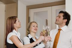 Three young businesspeople with sparkling wine glasses, toasting, clinking gl Stock Photos