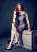 Portrait of well dressed woman sitting on an old suitcase Stock Photos
