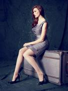 Portrait of well dressed woman sitting on an old suitcase - stock photo
