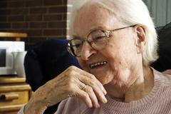 happy smiling elderly lady in an old-age home - stock photo