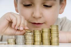 7 year-old boy counting stacks of coins, stacking coins Stock Photos