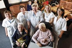 Residents and caretakers, nursing staff in the common room of a nursing home Stock Photos