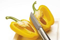 Yellow capsicum cut in half with a knife Stock Photos