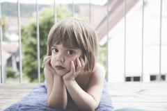 Portrait of sad little girl lying on towel on balcony - stock photo
