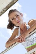 Portrait of smiling young woman leaning on a railing - stock photo