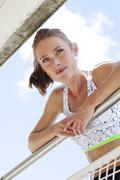 Portrait of young woman leaning on a railing Stock Photos