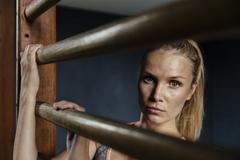 Stock Photo of Serious woman at wallbars in gym