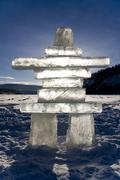 Stock Photo of ice figure of a man, inukshuk on the frozen yukon river, dawson city at back,