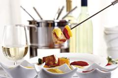 Fondue fork with meat, capsicum and dips in front of a fondue pot Stock Photos