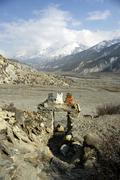 Painted stone gateway leading out into the barren manang valley, annapurna re Stock Photos