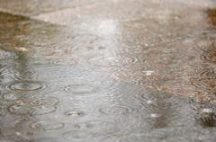 Raindrops falling in a puddle - stock photo