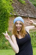 Portrait of smiling young woman with blue bonnet showing victory-sign with both - stock photo