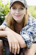 Portrait of a smiling young woman sitting on a lawn-mower - stock photo